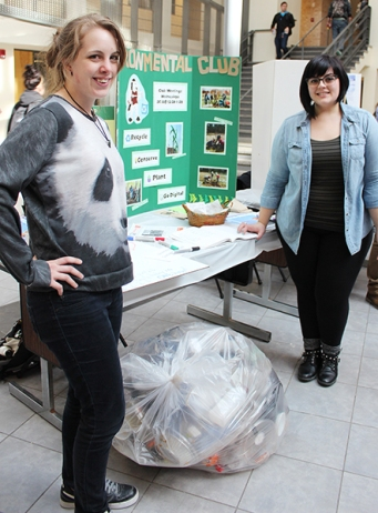 At a recent club fair, Montgomery County Community College Environmental Club Co-Presidents Natalya Martin (left) and Natalie DeSantis showcased the amount of recyclable materials that are mistakenly thrown in the trash during a given lunch hour at the Central Campus. Photo by Alana J. Mauger